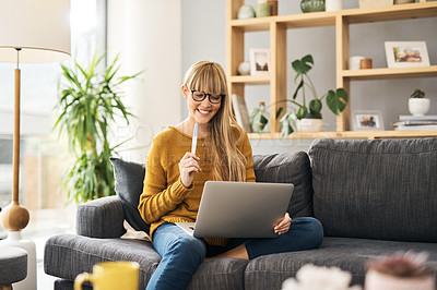 Buy stock photo Shot of a young woman using a laptop and pregnancy test on the sofa at home