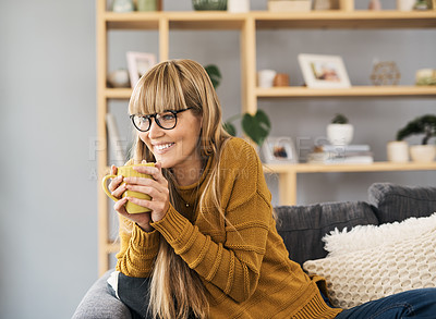 Buy stock photo Shot of a young woman having a relaxing coffee break on the sofa at home