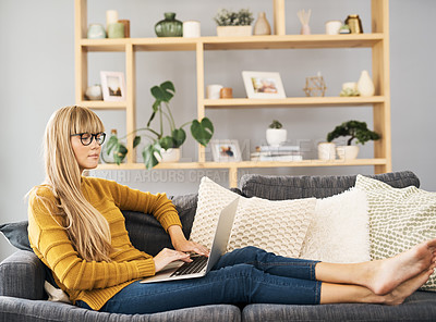 Buy stock photo Shot of a young woman using her laptop while relaxing on the sofa at home