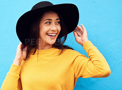 Buy stock photo Shot of a attractive young woman wearing a hat posing against a blue background