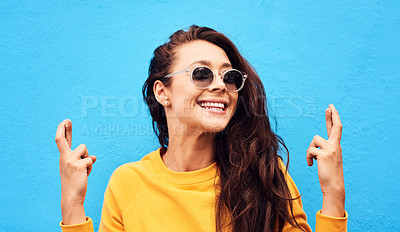 Buy stock photo Shot of a attractive young woman crossing her fingers while  posing against a blue background
