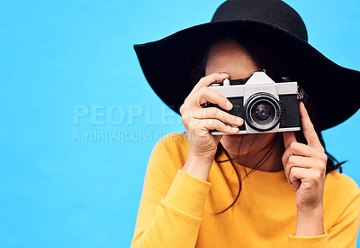 Buy stock photo Shot of a attractive young woman wearing a hat and taking a photo while posing against a blue background