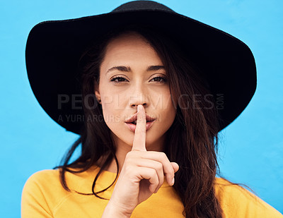 Buy stock photo Shot of a attractive young woman holding her finger over her mouth to keep silent while standing against a blue background