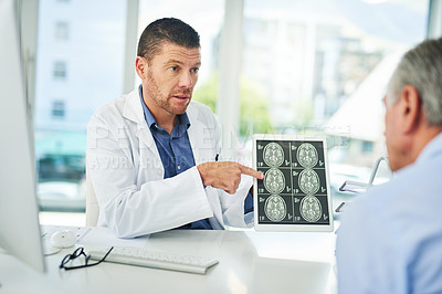 Buy stock photo Cropped shot of a focused middle aged doctor showing test results to a patient inside of his office during the day