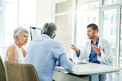 Buy stock photo Cropped shot of a focused middle aged doctor consoling with a patient inside of his office during the day
