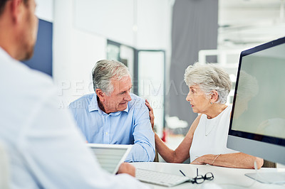 Buy stock photo Cropped shot of an elderly couple looking concerned and talking to each other inside of a doctor's office during the day