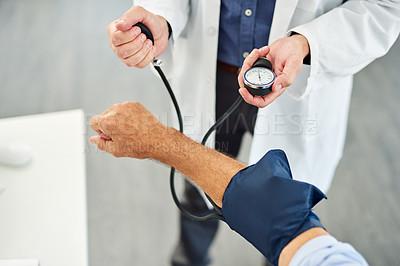 Buy stock photo Cropped shot of an unrecognizable doctor taking a blood pressure test on a patient inside of his office during the day
