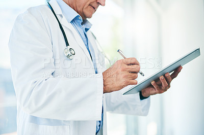 Buy stock photo Cropped shot of a unrecognizable elderly doctor making notes on a digital tablet in his office