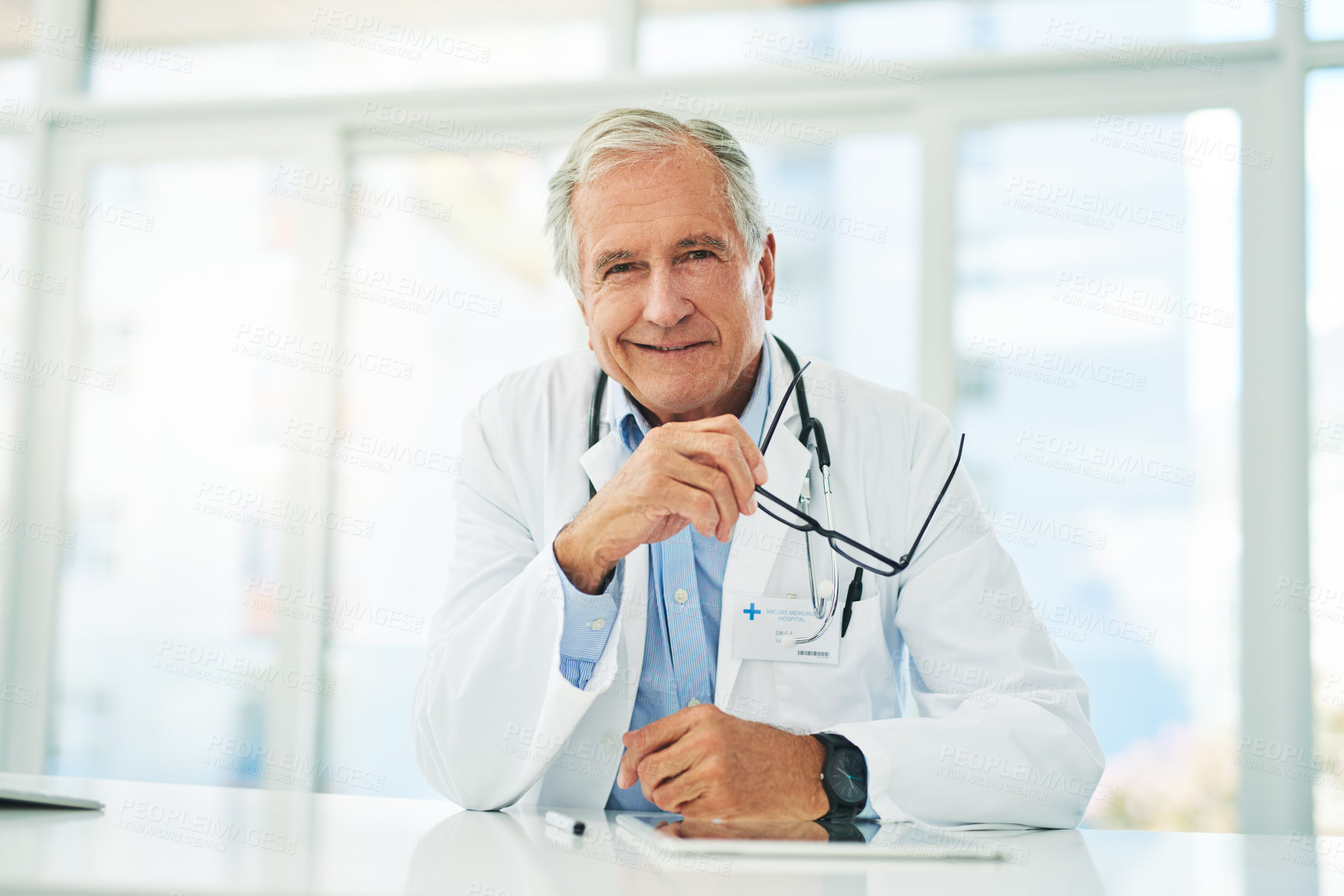 Buy stock photo Portrait of a cheerful elderly doctor seated at his desk while looking into the camera inside of his office during the day