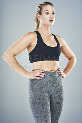 Buy stock photo Studio shot of a sporty young woman standing against a grey background