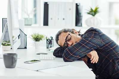 Buy stock photo Shot of a young designer sleeping at his desk in an office