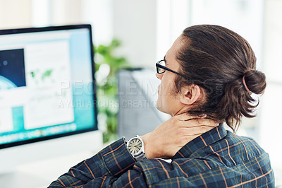 Buy stock photo Shot of a young designer suffering with neck pain while working in an office