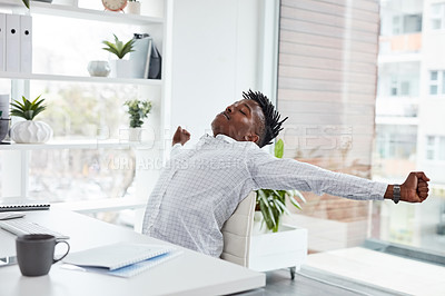 Buy stock photo Shot of a young businessman stretching while working in an office