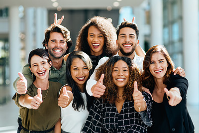 Buy stock photo Portrait of a group of cheerful businesspeople showing thumbs up inside of the office building during the day