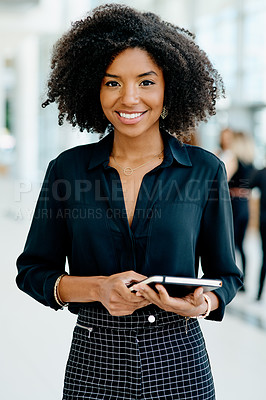 Buy stock photo Shot of a confident young businesswoman standing with a digital tablet in her hands inside of the office at work