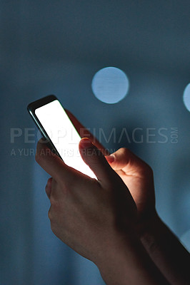 Buy stock photo Cropped shot of an unrecognizable businessman using his cellphone while working late at night in the office