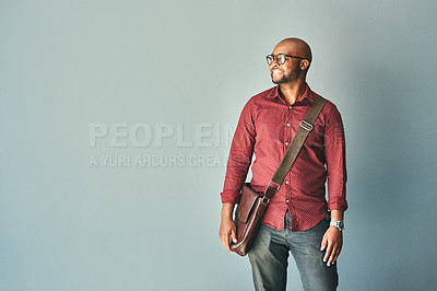 Buy stock photo Studio shot of a handsome young man wearing a messenger bag against a grey background