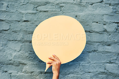 Buy stock photo Shot of an unrecognizable person holding a speech bubble against a brick wall outside during the day