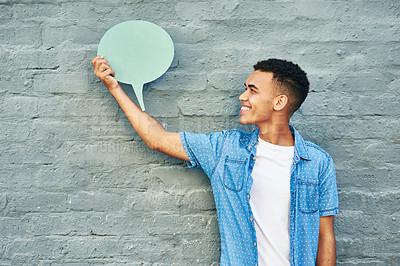 Buy stock photo Shot of a cheerful young man holding a speech bubble while standing against a brick wall