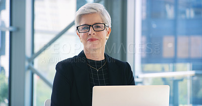 Buy stock photo Portrait of a mature businesswoman working on a laptop in an office