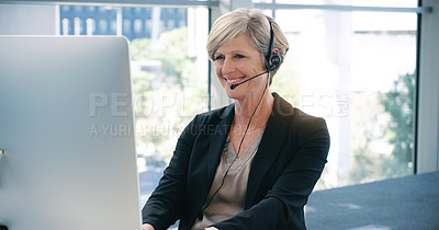 Buy stock photo Shot of a mature businesswoman wearing headphones while working on a computer in an office