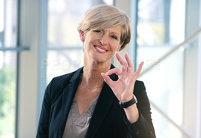 Buy stock photo Portrait of a mature businesswoman showing an ok sign in an office