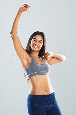 Buy stock photo Cropped studio portrait of an attractive young woman cheering with arms raised against a gray background
