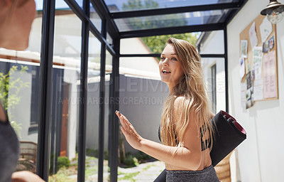 Buy stock photo Shot of a cheerful young woman saying goodbye to her friends after a yoga class inside of a studio