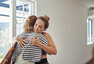 Buy stock photo Shot of a cheerful young woman hugging and welcoming her friend to a yoga class inside of a studio
