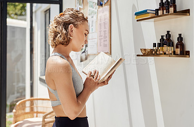 Buy stock photo Shot of a focused young woman reading a book outside of a yoga studio after a session workout
