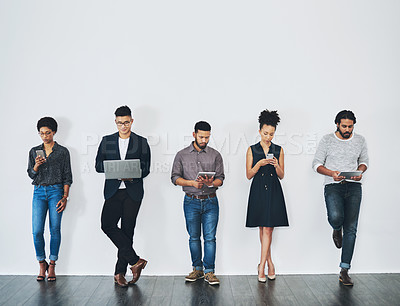 Buy stock photo Studio shot of a group of businesspeople using digital devices while waiting in line against a white background