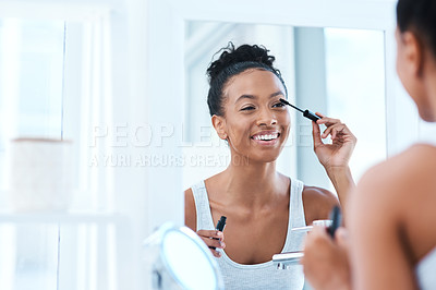 Buy stock photo Shot of a beautiful young woman applying mascara in her bathroom mirror
