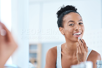 Buy stock photo Shot of a young woman applying lipstick in her bathroom mirror