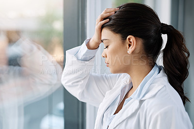 Buy stock photo Shot of a young female doctor looking stressed out while standing at a window in a hospital