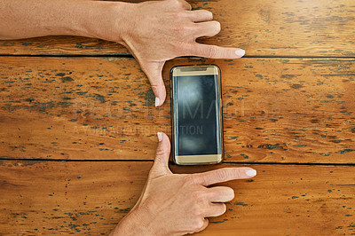 Buy stock photo High angle shot of a cellphone on top of a table with an unrecognizable person holding it on the sides making a frame with his fingers