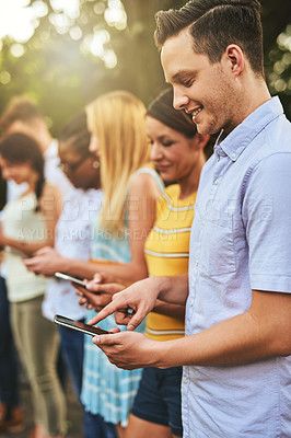 Buy stock photo Cropped shot of a group of young friends browsing on their cellphones outside during the day