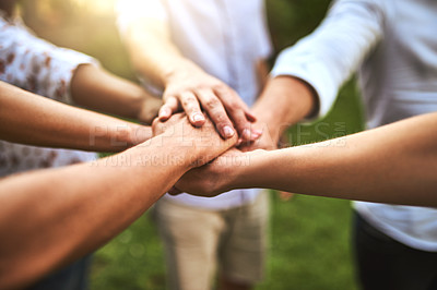Buy stock photo Closeup of a group of unrecognizable friends forming a huddle with their hands outside during the day