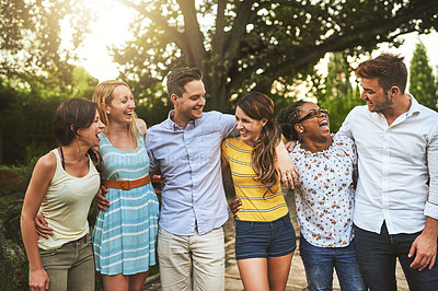 Buy stock photo Shot of a group of young friends standing  arms around outside during the day