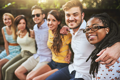 Buy stock photo Shot of a group of young friends sitting arms around outside during the day