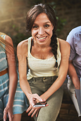 Buy stock photo Shot of a cheerful young woman seated next to her friends outside during the day