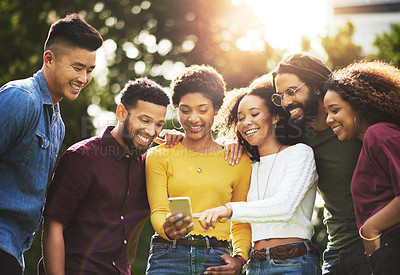 Buy stock photo Shot of a group of friends looking at something on a cellphone