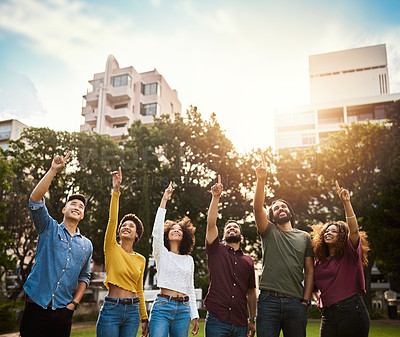 Buy stock photo Shot of a group of friends pointing up