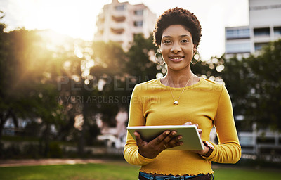 Buy stock photo Shot of a woman using a digital tablet outdoors