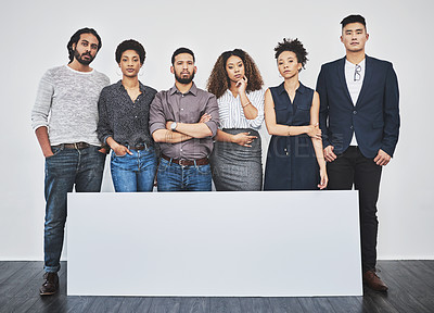 Buy stock photo Studio shot of a group of young businesspeople posing with a blank sign against a gray background