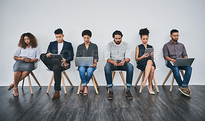 Buy stock photo Studio shot of a group of young businesspeople using wireless technology while waiting in line against a gray background