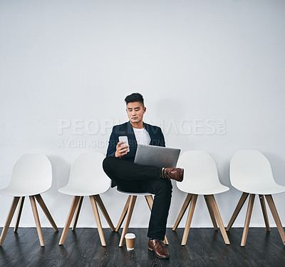 Buy stock photo Studio shot of a young businessman using a laptop and smartphone while waiting in line against a gray background