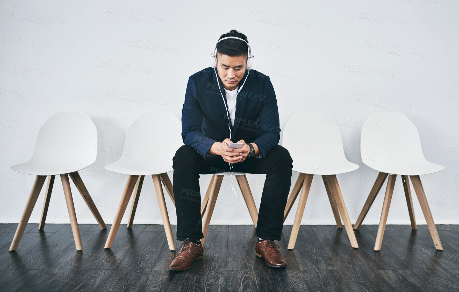 Buy stock photo Studio shot of a young businessman using a smartphone while waiting in line against a gray background