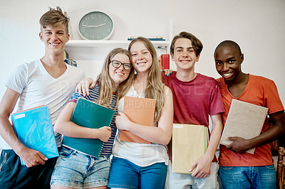 Buy stock photo Portrait of a group of cheerful young students seated in class while holding their school books inside during the day