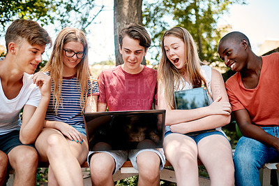 Buy stock photo Cropped shot of a group of confident young students seated outside in a park while looking at a laptop screen together