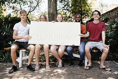 Buy stock photo Portrait of a group of cheerful young students holding a poster saying